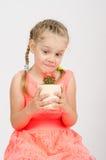 女孩凝视在罐的一个仙人掌 免版税库存照片