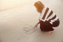 女孩凹道在海滩葡萄酒颜色口气的心脏形状 图库摄影