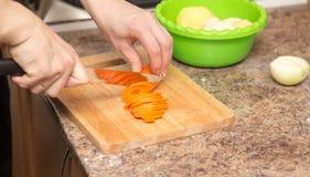 女孩切与一把刀子的一棵红萝卜在委员会 库存照片