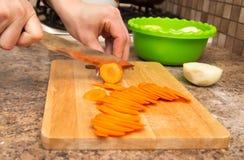 女孩切与一把刀子的一棵红萝卜在委员会 免版税库存图片