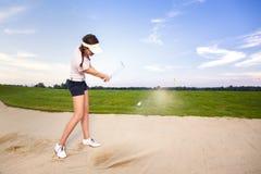 女孩切削在地堡的高尔夫球运动员球。 库存照片