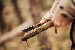 女孩切开一根棍子刀子 免版税图库摄影