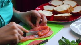 女孩切开三明治的三文鱼 在板材旁边是一个切的大面包和草本 在一个空白背景的特写镜头 影视素材