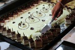 女孩切开白蛋糕 免版税库存图片