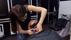 女孩刮胡子给美发师的一个人 影视素材