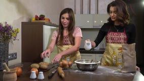 女孩剥土豆,并且第二名妇女倒牛奶入一碗面粉 影视素材