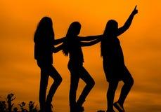 女孩剪影反对天空的在日落, 免版税库存图片
