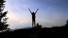 女孩剪影在山顶部的用手上升姿态 成功运气命中成就的概念和标志 股票视频