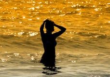 女孩剪影在海的 图库摄影