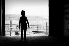 女孩剪影毂仓大门的 免版税库存照片