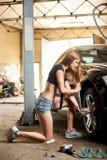 女孩加强一辆黑汽车的螺栓 库存照片