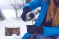 女孩加热与一杯茶或咖啡在冬天森林热的被仔细考虑的酒在杯子 库存图片