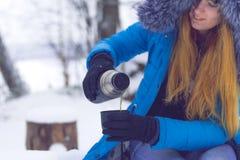 女孩加热与一杯茶或咖啡在冬天森林热的被仔细考虑的酒在杯子 免版税库存照片