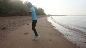 女孩努力去做在沿海滩的缓行在日出