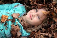 女孩包围的叶子堆 免版税库存图片