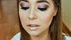 女孩化妆师绘女孩`嘴唇在柔和的桃红色颜色塑造的s 图库摄影