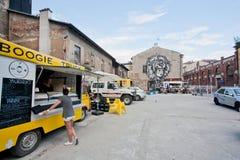女孩卖食物在轮子的小吃店在停车场 免版税库存照片