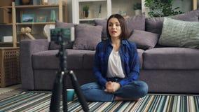 女孩博客作者有谈话的智能手机的录音录影在家拿着杯子 股票录像