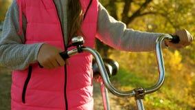 女孩卷自行车和握手弯曲轮子 孩子乘在途中的自行车旅行 体育走自行车的青少年的女孩 A 影视素材