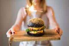 女孩厨师在她的手上拿着有的一个木切板黑cheesburgers 库存照片