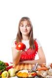 女孩厨师提供一个蕃茄 库存照片