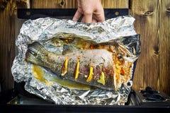 女孩去掉从一个电烤箱的` s手一条新近地被烘烤的鳟鱼 库存照片