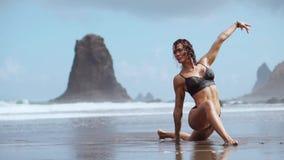 女孩参与在海洋的岸的舒展和体操 股票视频