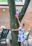 女孩发现一个复活节彩蛋在树 库存照片