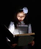 女孩发现了一本书。 免版税库存照片