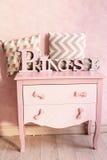 女孩变粉红色五斗橱有枕头的梳妆台 库存图片