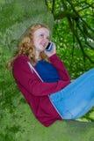 女孩叫与在绿色树的手机 免版税库存照片