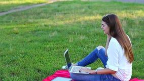 女孩叫使用膝上型计算机和挥动在绿草 股票录像