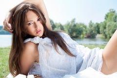 女孩可爱的草甸放松的年轻人 免版税库存图片