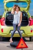 女孩司机和一个被刺的轮子 免版税图库摄影