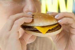 女孩吃一个开胃乳酪汉堡 库存图片