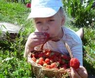 女孩吃一个草莓 免版税图库摄影