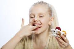 女孩吃一个蛋糕 库存图片