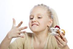女孩吃一个蛋糕 免版税图库摄影