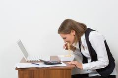 女孩吃一个面团,运作在膝上型计算机后 免版税库存图片