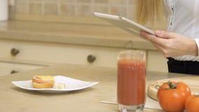 女孩吃三明治并且在厨房使用站立的片剂 股票录像