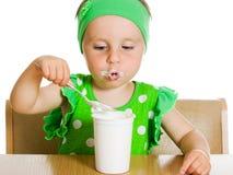 女孩吃与匙子奶制品。 免版税库存图片