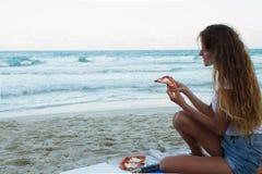 女孩吃在海滩,在海滩的一顿晚餐的薄饼 免版税库存照片