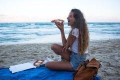 女孩吃在海滩,在海滩的一顿晚餐的薄饼 免版税图库摄影