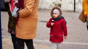 女孩吃在街道上的冰淇淋 秋天,凉快的天气 股票视频