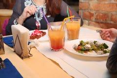 女孩吃在餐馆和饮料鸡尾酒的希腊沙拉 库存照片