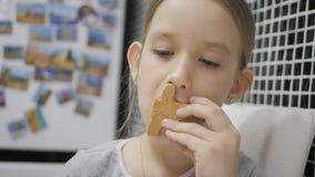 女孩吃坐在厨房里的姜饼曲奇饼 男孩节假日位置雪冬天 影视素材