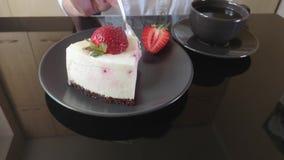 女孩吃奶油色果子蛋糕、蛋糕和一个杯子在一张黑玻璃桌上的无奶咖啡 影视素材