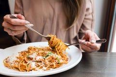 女孩吃意大利面团用蕃茄,肉 特写镜头意粉博洛涅塞风它在与匙子的一把叉子附近 巴马干酪 库存图片