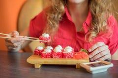 女孩吃日本食物保留与木chopsti的寿司卷 库存照片
