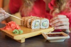 女孩吃日本食物保留与木chopsti的寿司卷 免版税库存照片